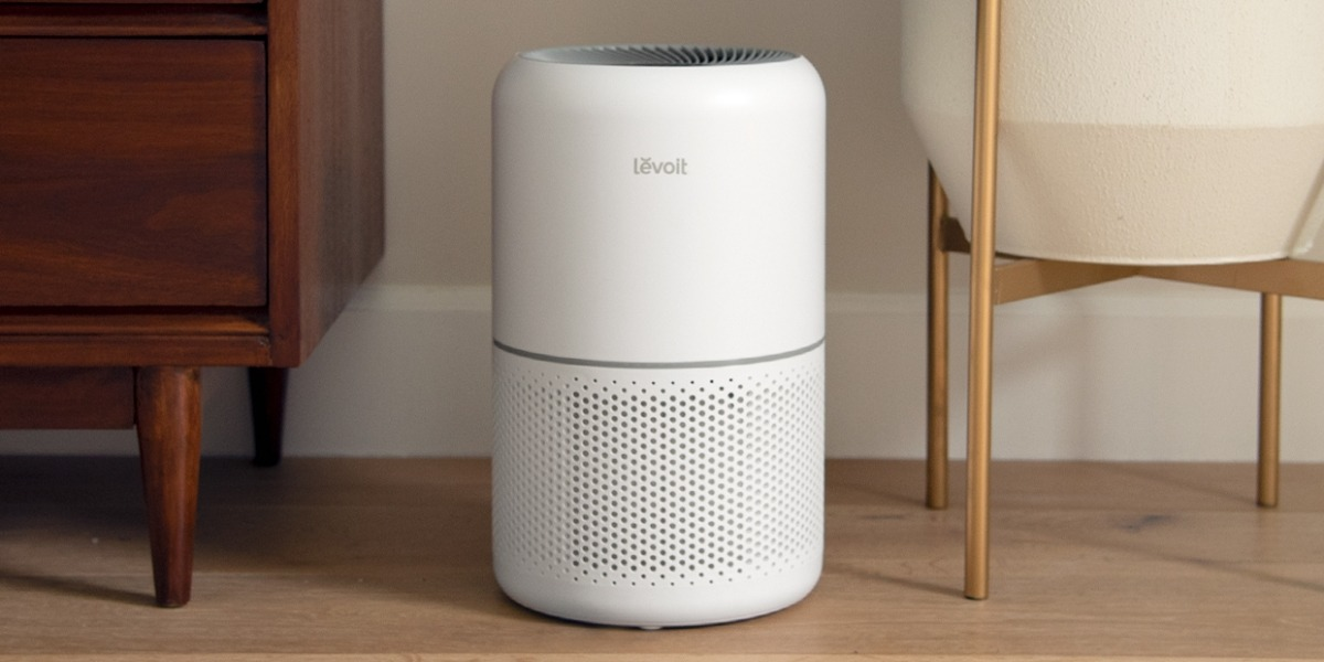 A white colored LEVOIT Air Purifier Core 300 on a wooden floor between furniture