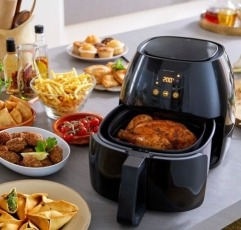 An air Fryer with a cooked chicken on a table and plates with delicious food all around it