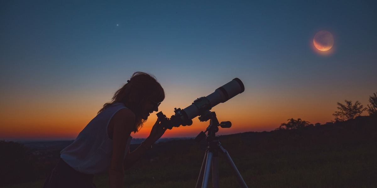 A woman looking at the sky through a telescope