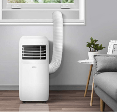 Midea 3-in-1 Portable Air Conditioner on wooden floor next to window